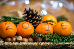 New Year 2016 is Coming Concept. Numbers written in Black Ink on the Oranges that are laying in the Basket with Hazelnuts, Pine Sticks and Xmas Lights on the stock photography