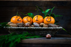 New Year 2018 is Coming Concept. Numbers written in Black Ink on the Oranges that are laying in the Basket with Pine Sticks and Nuts, Rustic Background royalty free stock photo