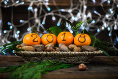 New Year 2018 is Coming Concept. Numbers written in Black Ink on the Oranges that are laying in the Basket with Pine Sticks, Nuts and Xmas Lights on the royalty free stock images