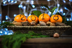 New Year 2018 is Coming Concept. Numbers written in Black Ink on the Oranges that are laying in the Basket with Pine Sticks, Nuts and Xmas Lights on the royalty free stock photo