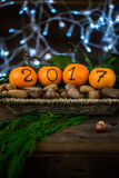 New Year 2017 is Coming Concept. Numbers written in Black Ink on the Oranges that are laying in the Basket with Pine Sticks, Nuts and Xmas Lights on the stock photography