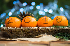 New Year 2016 is Coming Concept. Numbers written in Black Ink on the Oranges that are laying in the Basket with Pine Sticks and Xmas Lights on the Background stock photo