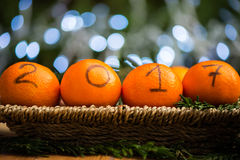 New Year 2017 is Coming Concept. Numbers written in Black Ink on the Oranges that are laying in the Basket with Pine Sticks and Xmas Lights on the Background stock images