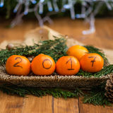 New Year 2017 is Coming Concept. Numbers written in Black Ink on the Oranges that are laying in the Basket with Pine Sticks and Xmas Lights on the Background royalty free stock images