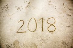 New Year 2018 is coming concept. wave coming to 2018 concept on the sand beach in the morning.Text 2018 on a beach sand. stock image
