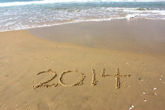 New Year 2014 is coming concept written on beach sand Royalty Free Stock Images