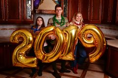 New 2019 Year is coming. Group of cheerful young people carrying. Gold colored numbers and have fun at the party royalty free stock photos