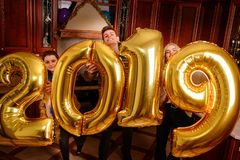 New 2019 Year is coming. Group of cheerful young people carrying gold colored numbers and have fun at the party.  stock images