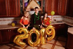 New 2019 Year is coming. Group of cheerful young people carrying. Gold colored numbers and have fun at the party stock image