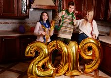New 2019 Year is coming. Group of cheerful young people carrying gold colored numbers and have fun at the party.  royalty free stock images
