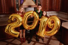 New 2019 Year is coming. Group of cheerful young people carrying. Gold colored numbers and have fun at the party royalty free stock photo