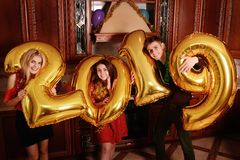New 2019 Year is coming. Group of cheerful young people carrying gold colored numbers and have fun at the party.  royalty free stock photo
