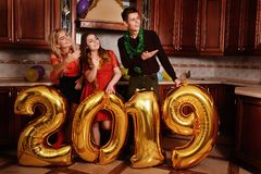 New 2019 Year is coming. Group of cheerful young people carrying gold colored numbers and have fun at the party.  stock photography