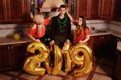 New 2019 Year is coming. Group of cheerful young people carrying. Gold colored numbers and have fun at the party royalty free stock image