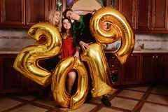 New 2019 Year is coming. Group of cheerful young people carrying gold colored numbers and have fun at the party royalty free stock image