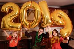 New 2019 Year is coming. Group of cheerful young people carrying gold colored numbers and have fun at the party.  royalty free stock photography