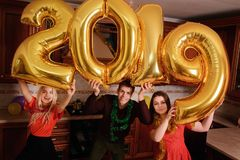 New 2019 Year is coming. Group of cheerful young people carrying gold colored numbers and have fun at the party.  stock photos