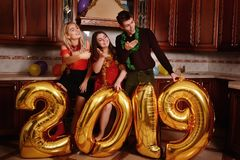 New 2019 Year is coming. Group of cheerful young people carrying gold colored numbers and have fun at the party.  royalty free stock image