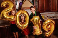 New 2019 Year is coming. Group of cheerful young people carrying gold colored numbers and have fun at the party.  royalty free stock photos