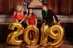New 2019 Year is coming. Group of cheerful young people carrying gold colored numbers and have fun at the party royalty free stock images