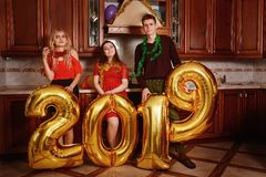 New 2019 Year is coming. Group of cheerful young people carrying gold colored numbers and have fun at the party stock photography