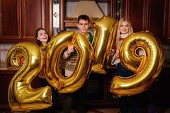 New 2019 Year is coming. Group of cheerful young people carrying. Gold colored numbers and have fun at the party stock photography