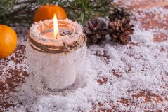 Burning candle, tangerines and fir branches on a wooden background Stock Photo