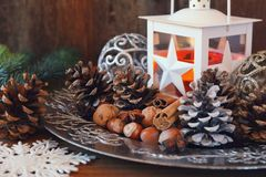 New Year composition: burning lantern, pine cones and Christmas tree decorations. Royalty Free Stock Photography