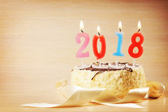 New Year 2018 composition. Cake and burning candles Stock Image