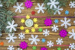 New Year composition with clock, snowflakes and fir branches. Colorful snowflakes and spruce branches lie on the wooden background stock photography