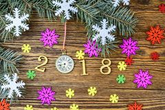 New Year composition with clock, snowflakes and fir branches. Happy New Year 2018 on a wooden background royalty free stock images