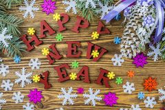New Year composition with greetings colorful snowflakes, fir con. Happy New Year on a wooden background royalty free stock photos