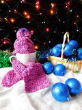 New Year composition made of mug, knitted kit and Christmas tree decorations. A mug for a hot drink decorated with knitted kit surrounded by Christmas royalty free stock image