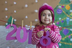 New Year 2018 concept. Beautiful small girl decorating the New Year numeral. background of a painted Christmas tree and Stock Image