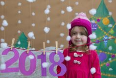 New Year 2018 concept. Beautiful small girl decorating the New Year numeral. background of a painted Christmas tree and Royalty Free Stock Image