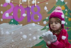 New Year 2018 concept. Beautiful small girl decorating the New Year numeral. background of a painted Christmas tree and Stock Images