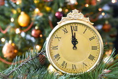 New year concept. New year celebration setting clock and christmas tree lights in the background Stock Images