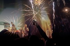 New Year concept - cheering crowd and fireworks Royalty Free Stock Photo