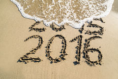 New year 2016 concept. Concept of coming 2016 year. Inscription of 2015 and 2016 written on sand with water sea foam covering 2015 year Royalty Free Stock Image