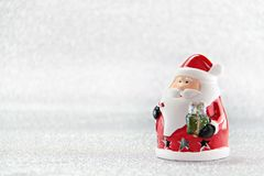 New Year concept : Cute santa claus doll on silver glitter paper background Royalty Free Stock Images