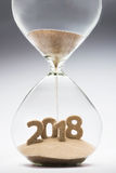 New Year 2018. Concept with hourglass falling sand taking the shape of a 2018 Royalty Free Stock Photo