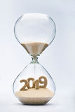 New Year 2019. Concept with hourglass falling sand taking the shape of a 2019 Stock Image