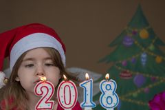 New Year 2018 concept. Pretty little girl in a Santa Claus hat blowing out candles - closeup shot Royalty Free Stock Photo