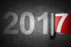 2017 New Year Concept. Ripped gray paper against red background with numbers 7 become 2017 Stock Image