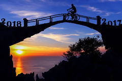 New year 2018 concept. Silhouette man and bicycle on the bridge. Stock Photo