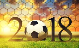 New Year 2018 concept. Soccer ball in grass at sunset Royalty Free Stock Image