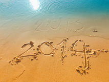New Year 2014 concept-written in sand on the beach. New Year's Eve 2013 and New Year 2014 on a beach sand Stock Images