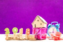 New year concepts,2018 Number with coins and house model on gift. Ribbon and watch placed on the side,violet background Stock Photography