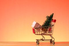 NEW YEAR CONCEPTUAL with shopping trolley,gift boxes and Christmas tree on a wooden table. NEW YEAR CONCEPTUAL with shopping trolley,gift boxes and Christmas royalty free stock photos