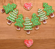 New year cookies. New year tree and christmas cookies on wooden background. With two hearts Royalty Free Stock Images